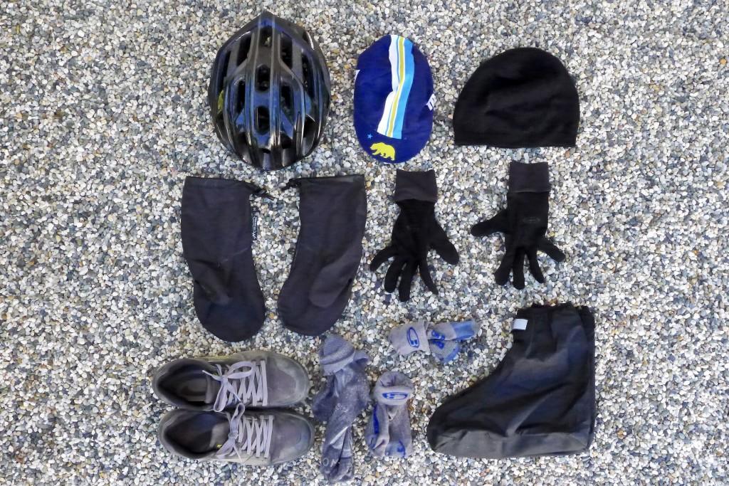 From top left: helmet, cycling cap, ski cap, rain mittens, wind gloves, sneakers, midweight sleep socks, two pair thin socks, rain booties