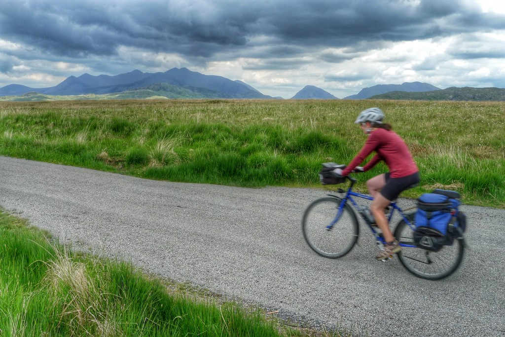 Carrie speeds by on some new chip seal with the McGillicuddy Reeks as a backdrop.