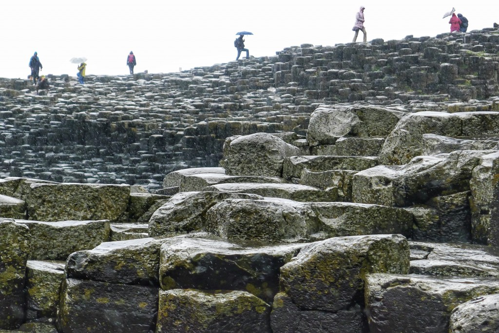 Tourists clamor over the slippery rocks at the Giant's Causeway.