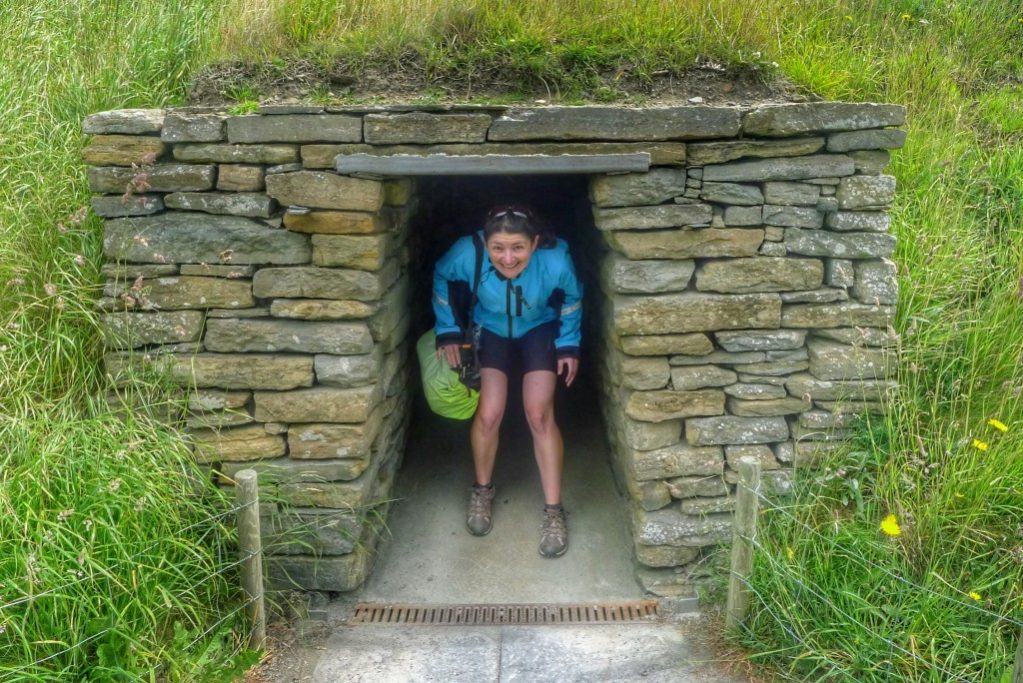 Carrie emerges from a replica building at Skara Brae.