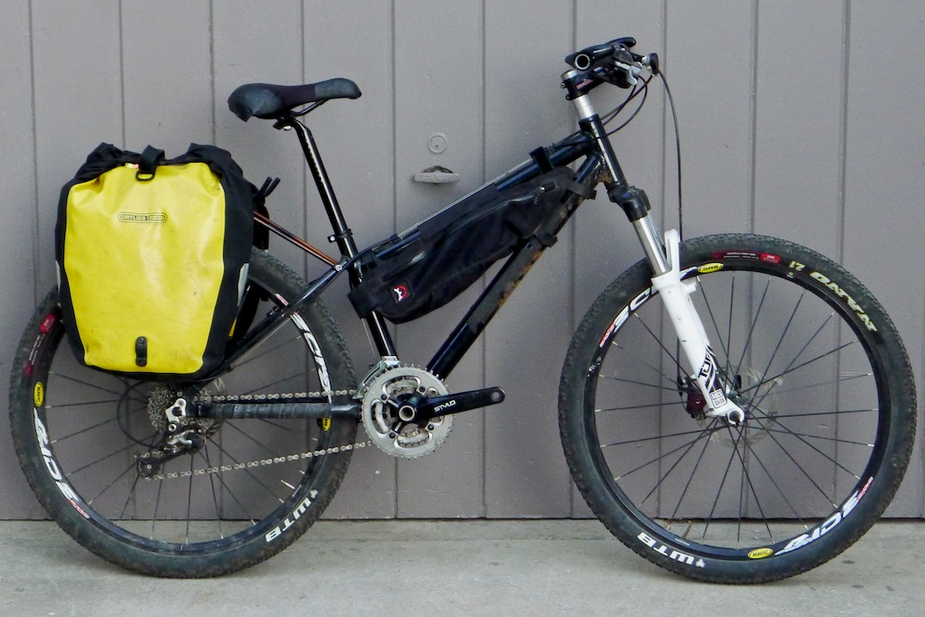 "Carrie rides a 26"" hardtail with a pair of Ortlieb back roller classics and a Revelate Tangle frame bag that will house her 2L water bladder."