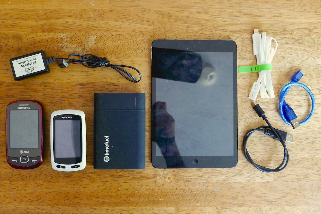 From left to right: cell phone, Sinewave Cycles Revolution USB dynamo adapter, Garmin Edge Touring GPS unit, Limefuel battery, iPad Mini, USB cables. All of this is stashed in the Revelate Pocket on my handlebars.