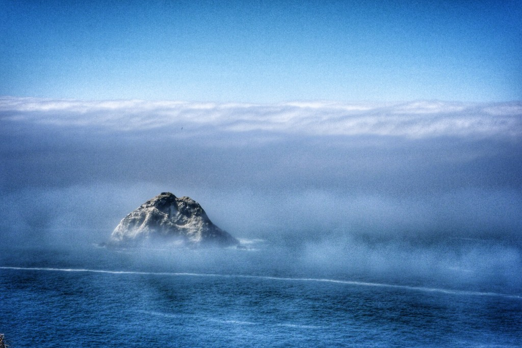 A rock juts out from the ocean and the incoming fog on the coast off Trinidad.