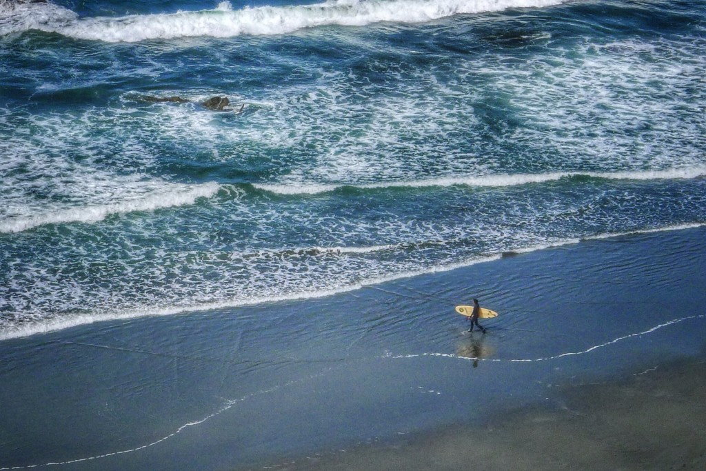 A surfer is about to brave the frigid water of the Pacific Ocean.